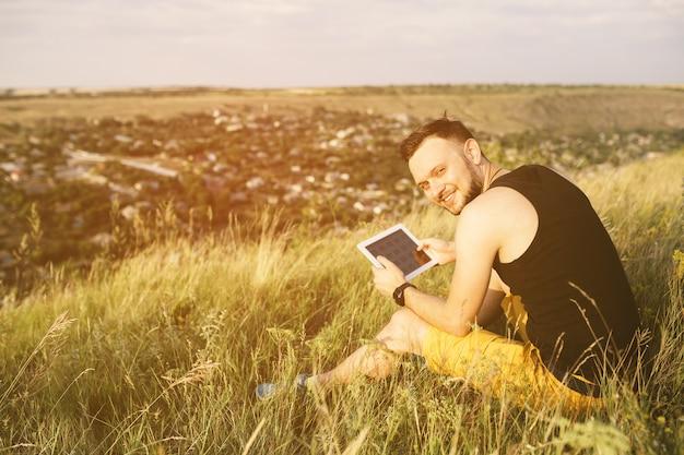 Hombre que trabaja al aire libre con la almohadilla de la tableta. filtro de instagram vintage retro