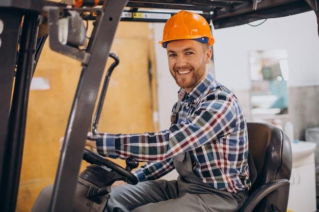 Hombre que trabaja en el almacén y la conducción de montacargas