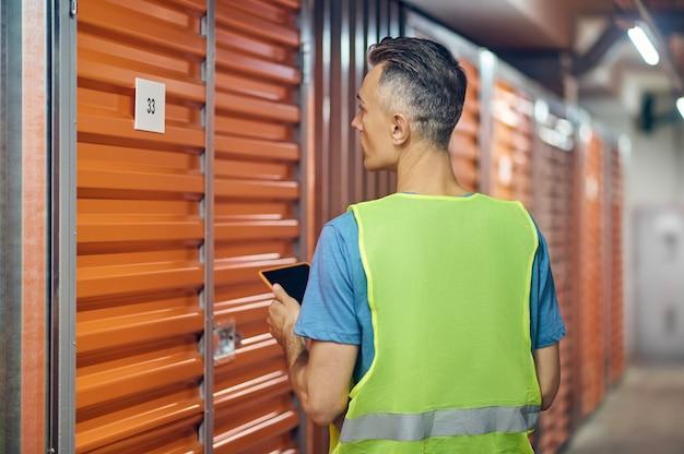 Hombre que trabaja en el almacén de guardia de pie con la espalda