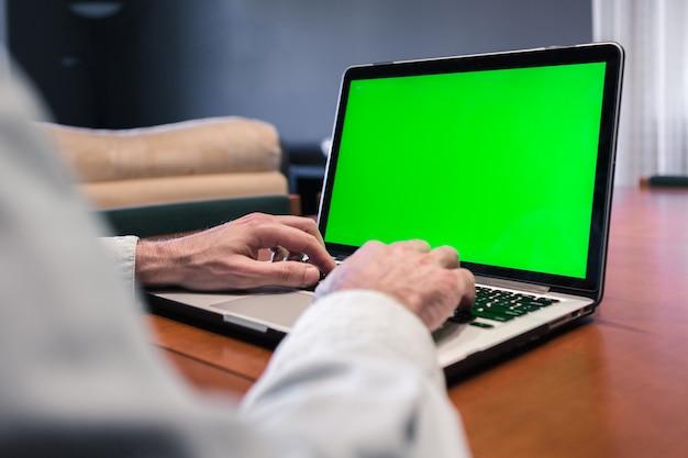Hombre que trabaja en casa en una computadora con pantalla verde.