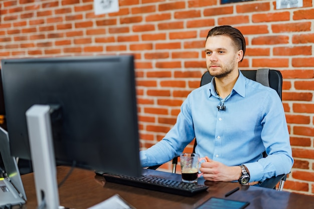 Hombre que trabaja con la computadora en la oficina de la empresa.