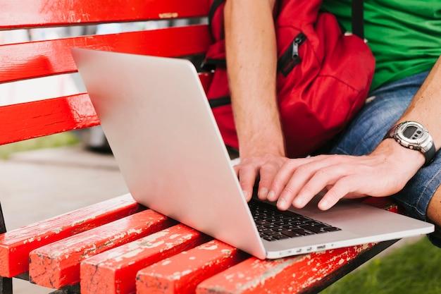 Hombre que trabaja en la computadora portátil en el banco