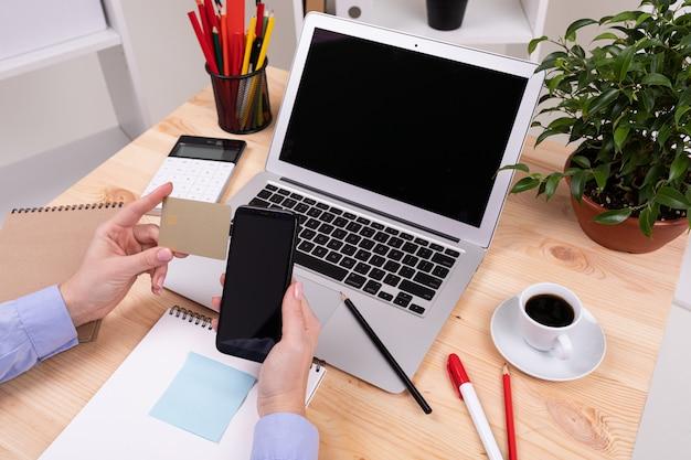 Un hombre que trabaja con computadora portátil, calculadora, bolígrafos, lápices, tarjetas, teléfonos y una planta en su escritorio en su oficina