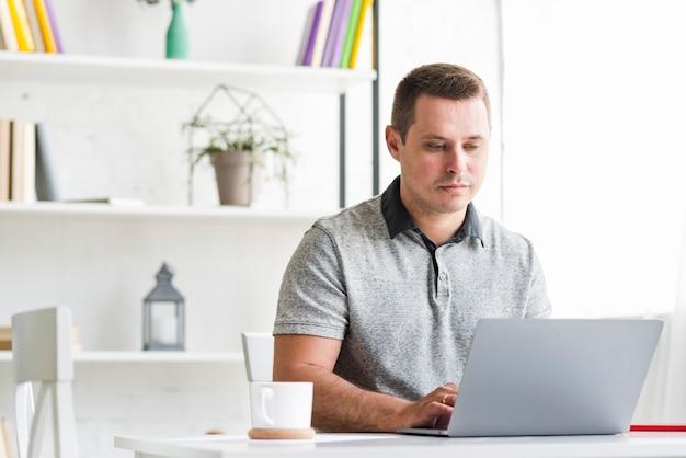 Hombre que trabaja en la computadora portátil en casa
