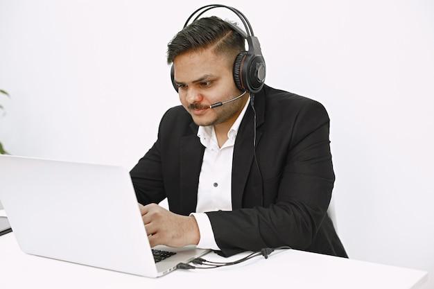Hombre que trabaja con la computadora portátil. despachador indio o trabajador de línea directa.