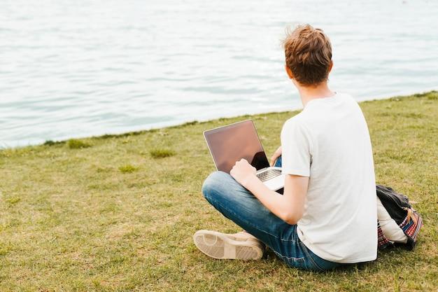 Hombre que trabaja en la computadora portátil por el lago