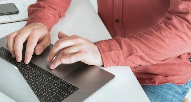Hombre que trabaja en la computadora portátil en la oficina en casa. trabajar en concepto de oficina en casa
