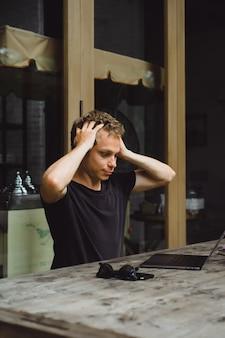 Hombre que trabaja con una computadora portátil en un café en una mesa de madera