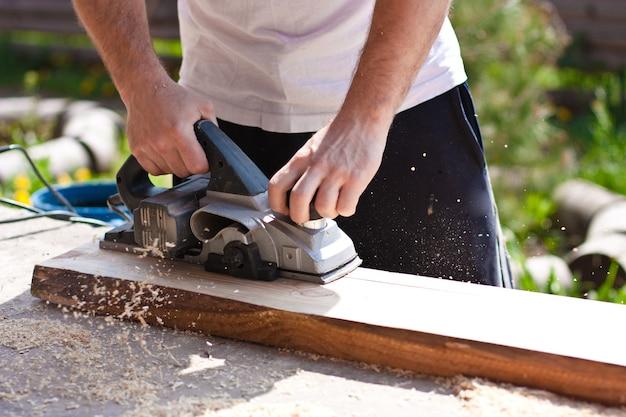 Hombre que trabaja con herramientas y tablas de madera
