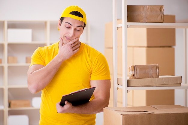 Hombre que trabaja en la oficina de servicios de paquetería postal