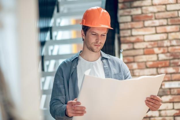 Hombre que trabaja con el plan de construcción en la función de construcción