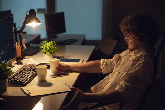 Hombre que trabaja solo en la oficina durante el coronavirus o la cuarentena covid-19, quedando hasta altas horas de la noche