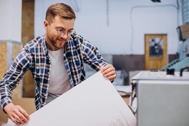Hombre que trabajaba en la imprenta con papel y pinturas
