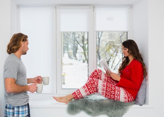 Hombre que trae la taza de café a la mujer sentada en el alféizar de la ventana leyendo un libro