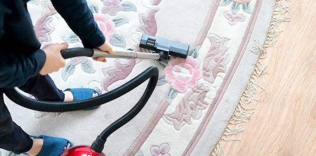 Un hombre que usa una aspiradora para limpiar la alfombra en casa