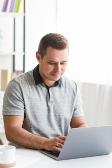 Hombre que usa la computadora portátil sobre el escritorio