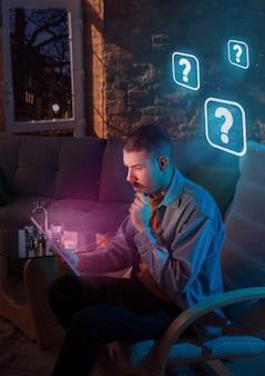Hombre que usa un gadget y recibe notificaciones de neón en casa por la noche. sentado en un sillón, sirviendo en internet y buscando información. abuso de las redes sociales, chatear y navegar, adicción a los dispositivos.