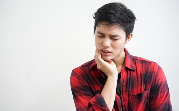 Hombre que usa la mano en la mejilla para aliviar el dolor de la muela del juicio