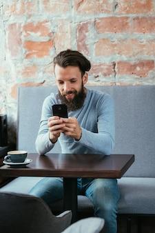 Hombre que usa el mensaje de lectura del teléfono móvil o blogs en café. estilo de vida ocioso y ocio.