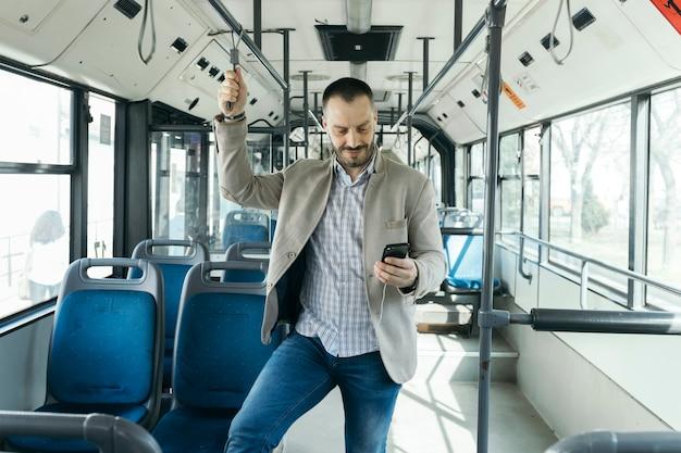 Hombre que usa el teléfono inteligente en el autobús