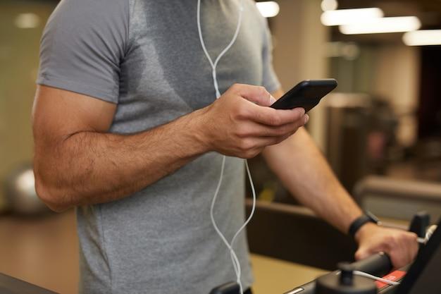 Hombre que usa el teléfono inteligente en el gimnasio closeup
