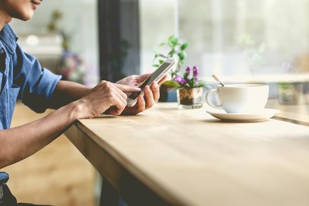 Hombre que usa el teléfono inteligente móvil en la cafetería.