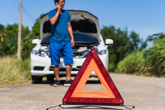 Un hombre que usa un teléfono mientras tiene un auto problemático y una señal de advertencia de triángulo rojo en la carretera