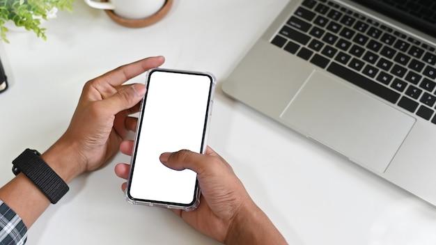 Hombre que usa el teléfono móvil de la maqueta en el escritorio de oficina con la exhibición del camino de recortes.