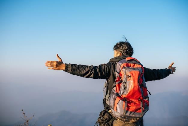 Hombre que viaja con mochila de senderismo en las montañas