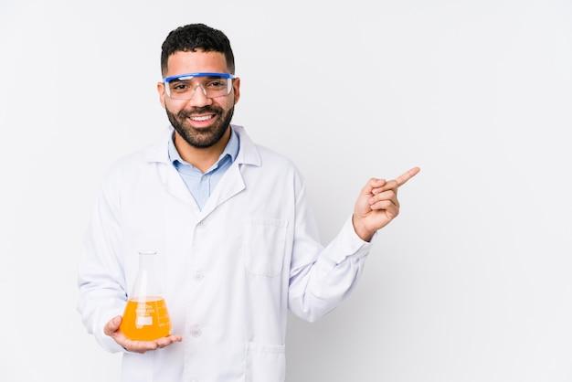 El hombre químico árabe joven aisló sonriendo y señalando a un lado, mostrando algo en el espacio en blanco.