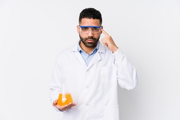 Hombre químico árabe joven que señala el templo con el dedo, pensando