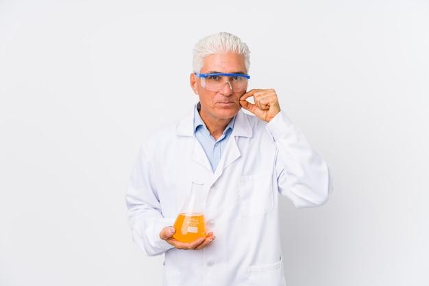 Hombre químico maduro aislado con los dedos en los labios manteniendo un secreto.