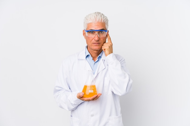 El hombre químico maduro aisló señalar el templo con el dedo, pensando, centrado en una tarea.