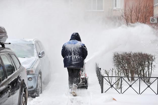 El hombre quita la nieve en el patio de un edificio de varios pisos con máquinas de nieve.