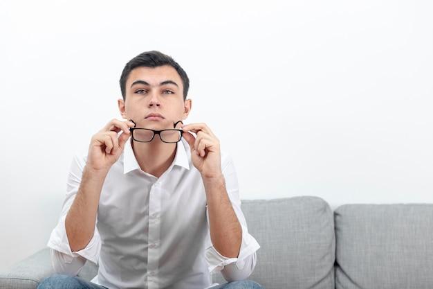 Hombre quitándose las gafas con espacio de copia