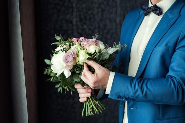 Hombre con ramo de novia en las manos, el novio preparándose en la mañana antes de la ceremonia de boda