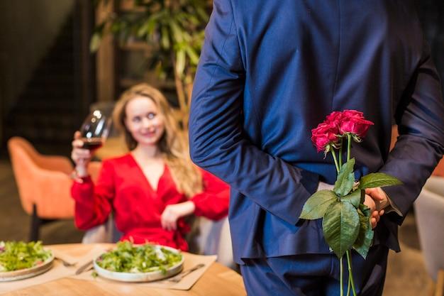 Hombre con ramo de rosas en la espalda