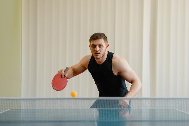 Hombre con raqueta y pelota jugando al ping pong en interiores