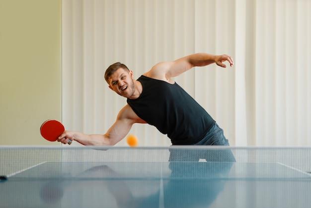 Hombre con raqueta de ping pong juega la pelota, imagen en acción, entrenamiento en interiores.