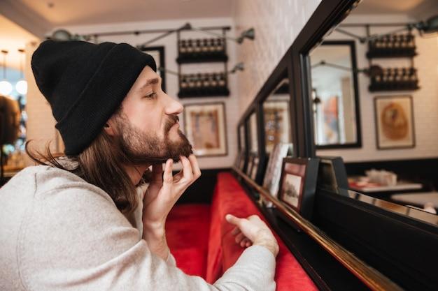 Hombre rascándose la barba cerca del espejo