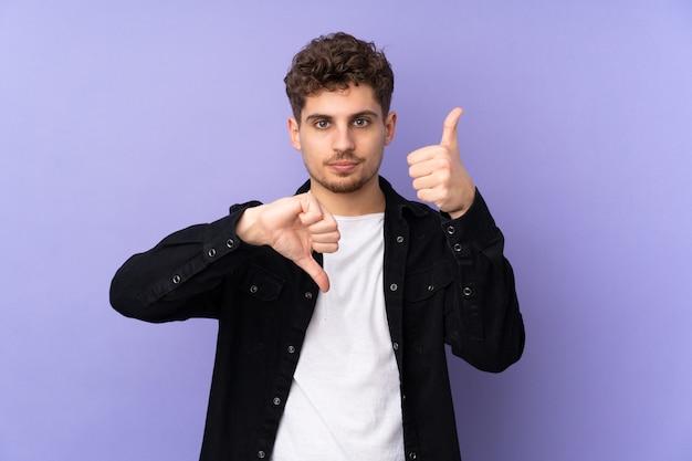 Hombre de raza blanca en la pared púrpura haciendo buena-mala señal