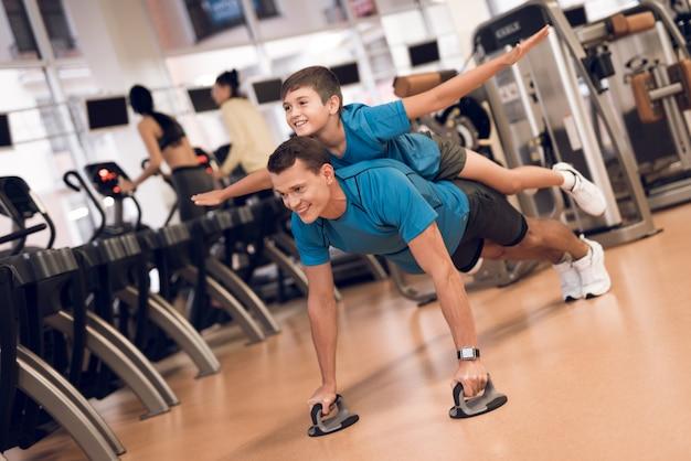 Un hombre realiza flexiones mientras su hijo yace sobre él.