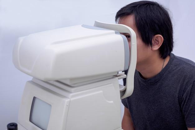 El hombre realiza una prueba ocular con una máquina de prueba ocular óptica