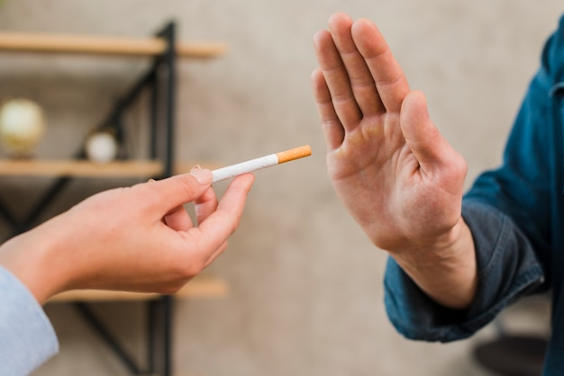 Hombre rechazando los cigarrillos ofrecidos por su colega.