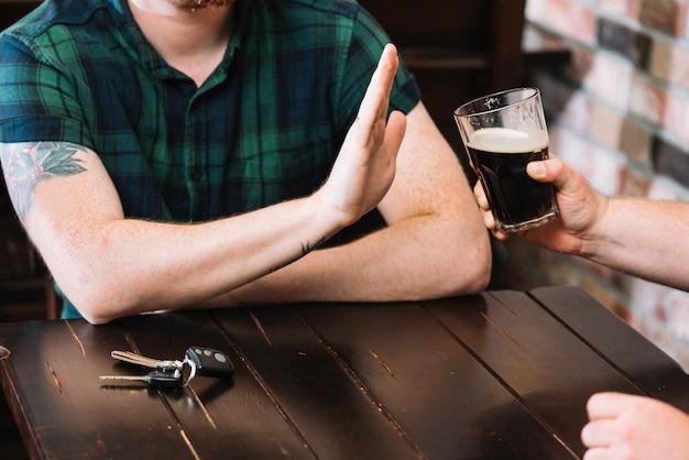 Hombre rechazando vaso de ron ofrecido por su amigo