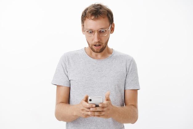 El hombre recibe un mensaje impactante mirando con sacudida la pantalla del teléfono inteligente, ojos saltones y boca abierta posando con una camiseta gris y gafas intensa y aturdida sobre una pared blanca
