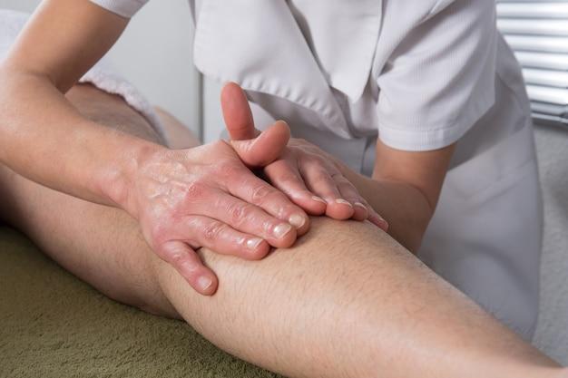 Hombre recibiendo un masaje ayurvédico en sus piernas