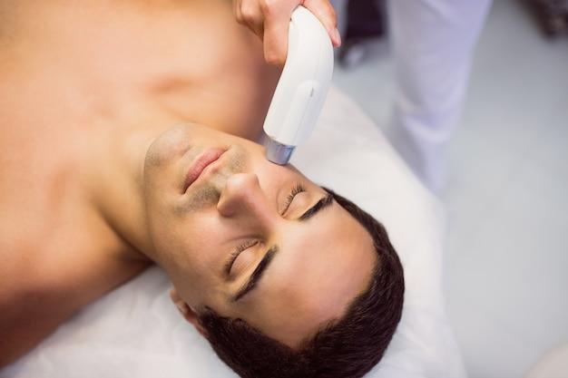 Hombre recibiendo un masaje facial en la clínica
