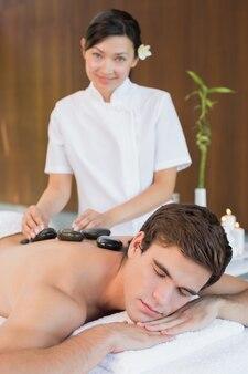 Hombre recibiendo masaje con piedras en el centro de spa