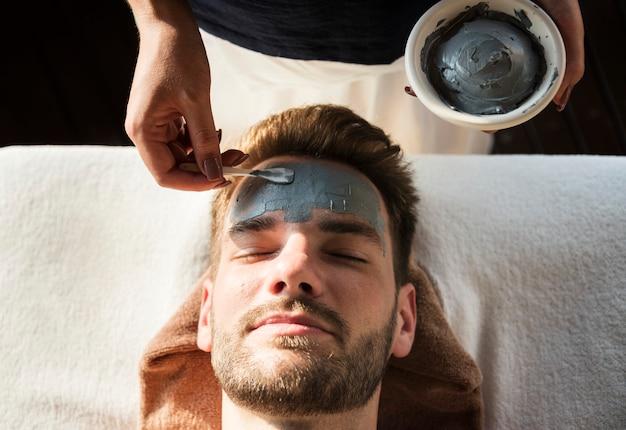 Hombre recibiendo una máscara de barro en un spa